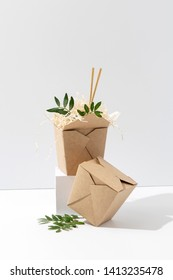 Disposable, compostable, recyclable paper hot food boxes with saw shawings and rowan branches in them over white background. Up close