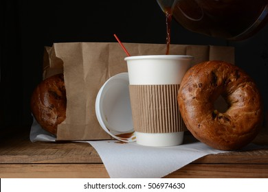 A disposable cup of coffee and bag of bagels. A to-go breakfast meal