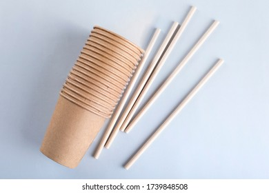 Disposable cups and drinking straws on light grey background.