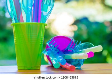 Disposable cutlery, cups and drinking tubes made of plastic are on a table