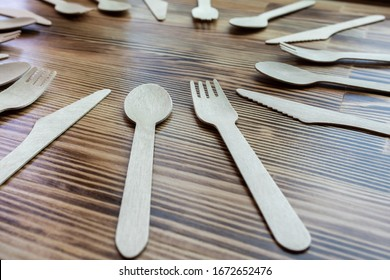 Disposable cutlery, dishes made from natural materials, wooden spoon, fork, knife on a wooden background, environmentally friendly. Place for text. mock up