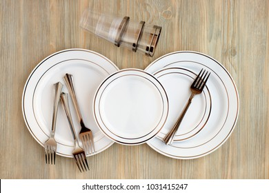 Disposable dishes for a picnic. A set of dishes made of plastic. View from above. Plastic plates, glasses, picnic forks. Disposable plates and mugs for eating in nature. Plastic tableware for a picnic