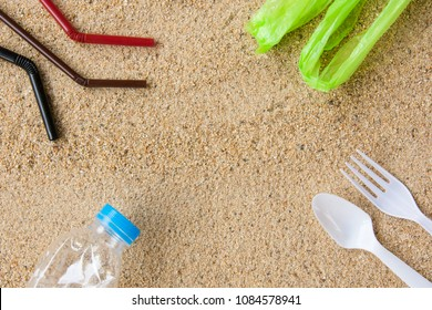 Disposable fork, spoon, water bottle, straws and bag on sandy beach background. Plastic pollution affecting marine ecology. Environment concept. Top view with copy space.