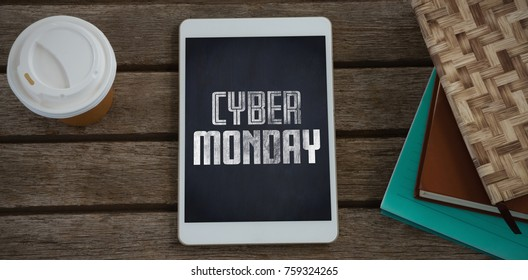 Disposable glass, books and digital tablet on wooden plank against title for celebration of cyber monday