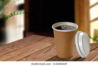 Disposable paper cup of coffee to go on wooden table at cafe.