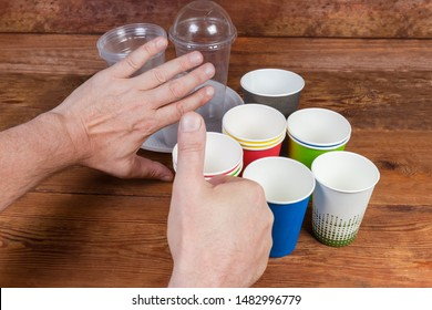 Disposable paper cups and plastic tableware on rustic table. Hand gestures approving to use disposable paper cups and renounce plastic tableware, concept