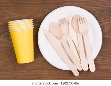 Disposable paper plates and cups and wooden cutlery on wooden table