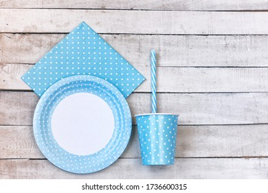 disposable paper utensils, plate, glass with straw, napkin on white wooden table, top view