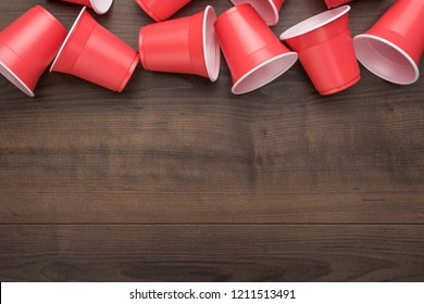 disposable plastic cups on the wooden background. top view of used plastic cups on the table. end of the party concept with copy space