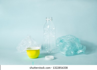 Disposable plastic items of every day use on blue background. Concept of ecological footprint of human: plastic bottle cap and food packaging that don't get recycled