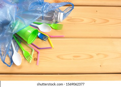 Disposable plastic utensils are scattered on wooden background. Ecology problem. Environmental pollution. Flat lay. Top view. Copy space.