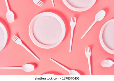 Disposable plastic utensils scattered on pink background. Concept of save environment, ecology, recreation on picnic, party and other events. Top view
