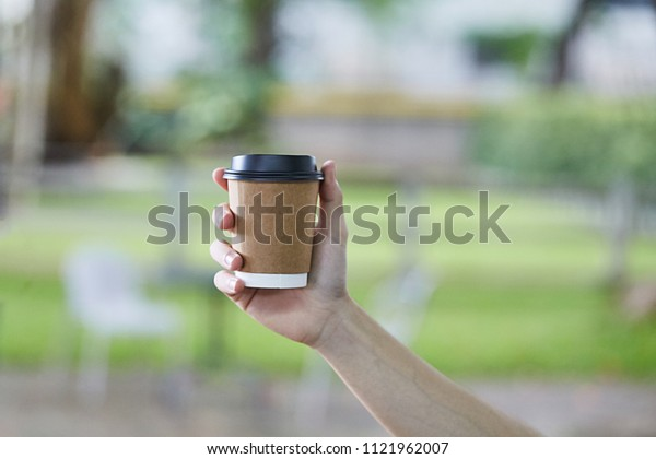 Disposable plastic White Coffee Cup with Black Lid holding on hand for takeaway on a blur green Background