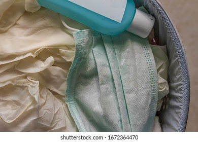 Disposable  Protective Surgical Mask And Gloves. Surgical mask , gloves  and an empty bottle of antiseptic gel in dustbin. Stock Image.
