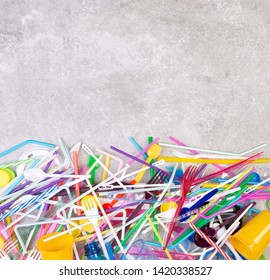 Disposable single use plastic objects such as bottles, cups, forks, spoons and drinking straws that cause pollution of the environment, especially oceans. Top view with copy space