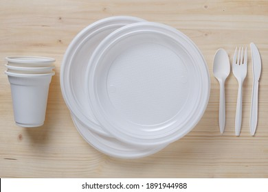 Disposable tableware and cutlery on wooden background, top view