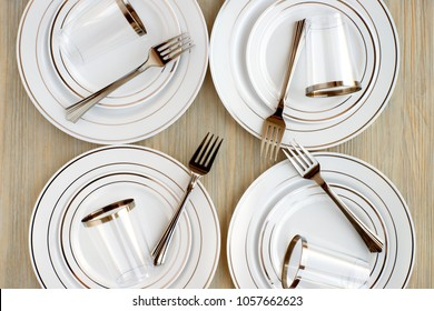 Disposable tableware for four persons. A set of plastic disposable dishes for a picnic. View from above. Plates, glasses and forks for outdoor recreation. Disposable tableware on a wooden background.