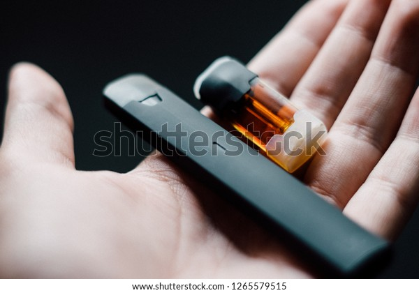 Disposable vape pen with refill pod on hand
