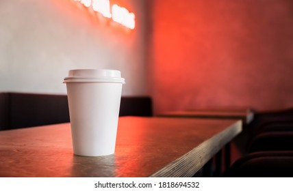 A disposable white paper coffee cup stands on the table of a trendy cafe with neon light.