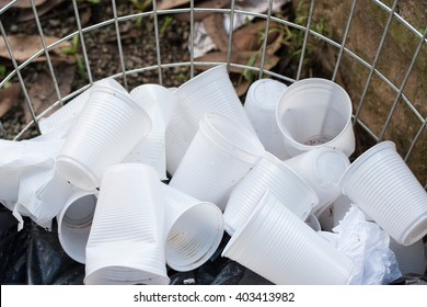 Disposable white plastic cups in open garbage container
