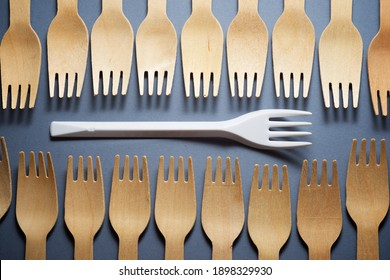 Disposable wooden and plastic cutlery on a table.