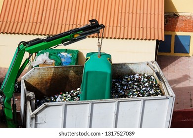 Disposal truck collects recycable mixed glass bottles from container. Waste Management, garbage truck