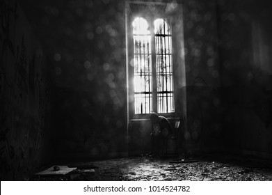 Disquieting presence near the window in one of the innumerable rooms, the ghost of a patient inside the psychiatric hospital of Volterra. Tuscany, Italy