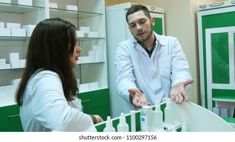 Dissapointed team of apothecaries in pharmacy standing in front of shelf talking