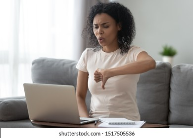Dissatisfied african woman sit on couch looking at computer screen showing thumbs finger down vlogger at live communications express negative opinion about services or products to subscribers concept
