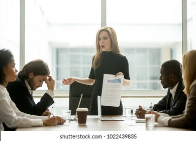 Dissatisfied angry female executive scolding african employee for bad work at diverse group meeting, white woman boss reprimanding black subordinate for poor financial result at office team briefing