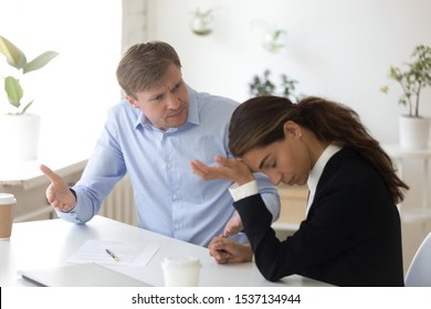 Dissatisfied angry middle aged male boss looking at stressed mixed race female employee, sitting together at workplace. Mad team leader blaming incompetent intern trainee, misunderstanding at office.