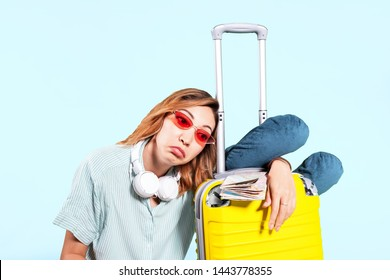 Dissatisfied Asian girl with a suitcase ready to travel expresses a sad emotion. The concept of a flight cancellation, and travel and sleeplessness on the trip