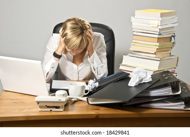 Dissatisfied business lady or student sitting at a busy  desk.