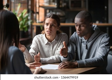Dissatisfied couple customers having claim about contract conditions, diverse clients sitting at table disputing with agent about mortgage loan or real estate problem, fraud and bad contractor concept