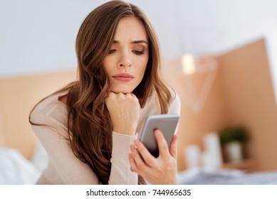 Dissatisfied girl using smartphone indoors