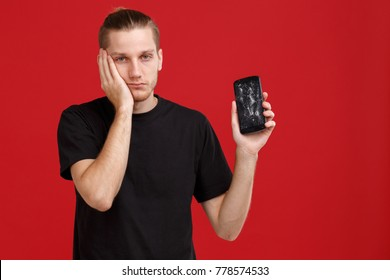 The dissatisfied guy is in a black T-shirt, is holding a broken mobile phone in his hands and is unhappy with his face.