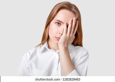Dissatisfied hopeless blue eyed woman covers face with palm, has long hair, wears elegant shirt, looks stresfully at camera, models against white background. Negative human facial expressions