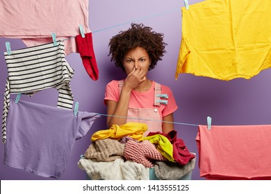 Dissatisfied housewife covers nose from stench, holds basin with dirty laundry, hangs wet clothes on clothes line, frowns face in displeasure, isolated on purple background. Housekeeping concept