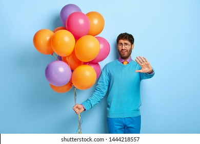 Dissatisfied man celebrates anniversary of birth, shows refusal gesture, doesnt want to be photographed, frowns face, wears spectacles, poses with colorful balloons. Guy with party attributes