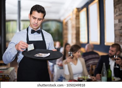 dissatisfied man waiter keeps money for the order in the restaurant