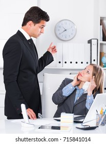 Dissatisfied manager scolding frustrated female assistant in office