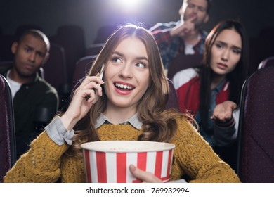 dissatisfied people looking at woman talking on smartphone in cinema