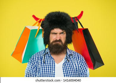 Dissatisfied with purchase. Unhappy hipster with his purchase in paperbags hanging on bull horns. Brutal bearded man with personal purchase. Buying fashion purchase.