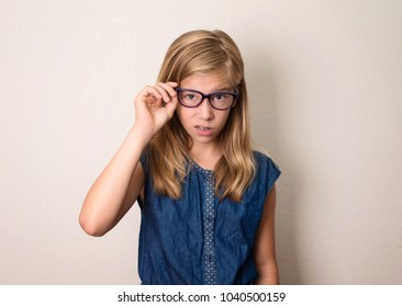 Dissatisfied teen girl looks suspiciously, sceptical, wearing glasses.