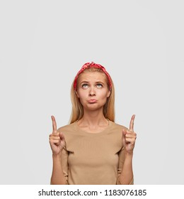 Dissatisfied teenager indicates upwards, has stressful negative facial expression, feels offense, regrets about something, advertises new item above head, suggests use blank space for promotion