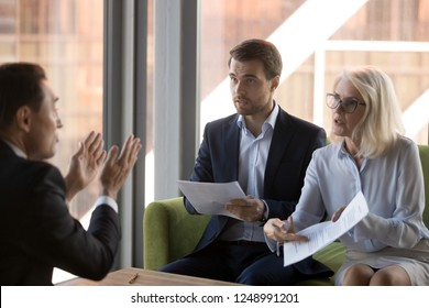 Dissatisfied woman financier director criticizing financial report or wrong agreement accusing man employee, colleague deny his guilt. Unqualified worker conflict problems and mistakes at work concept