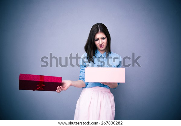 Dissatisfied woman opening gift over gray background