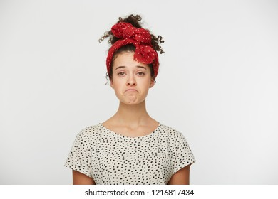 Dissatisfied young female pursed lower lip, being abused by something unpleasant, has unhappy expression, dressed tshirt with black polka dots, stands indoor against white wall