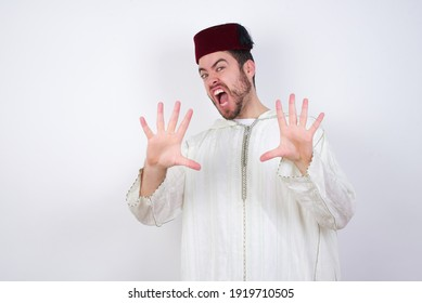 Dissatisfied young handsome Caucasian man wearing Arab djellaba and Fez hat over white wall frowns face, has disgusting expression, shows tongue, expresses non compliance, irritated with somebody.