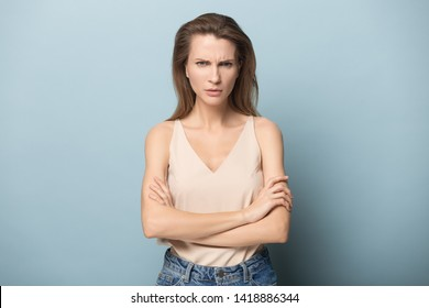 Dissatisfied young woman standing in closed posture with crossed hands, looking angrily at camera, showing irritated face expression, negative mood, posing on blue studio background.